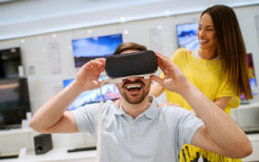 Young satisfied happy handsome man testing VR goggles while his smiling girlfriend standing behind and supporting him in a tech store.